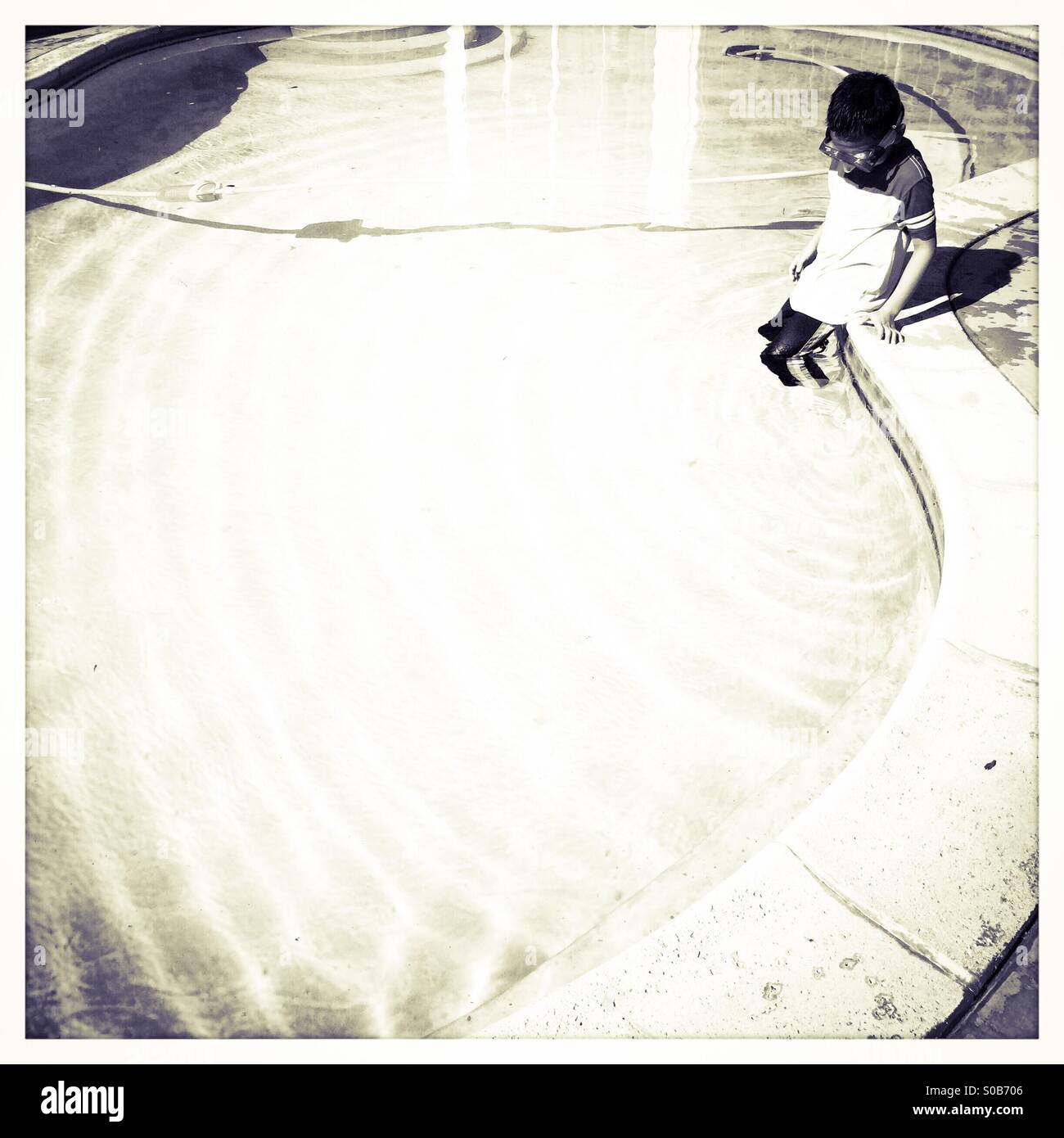A seven year old boy wearing clothes and a swimming mask sits on the edge of a swimming pool. Stock Photo