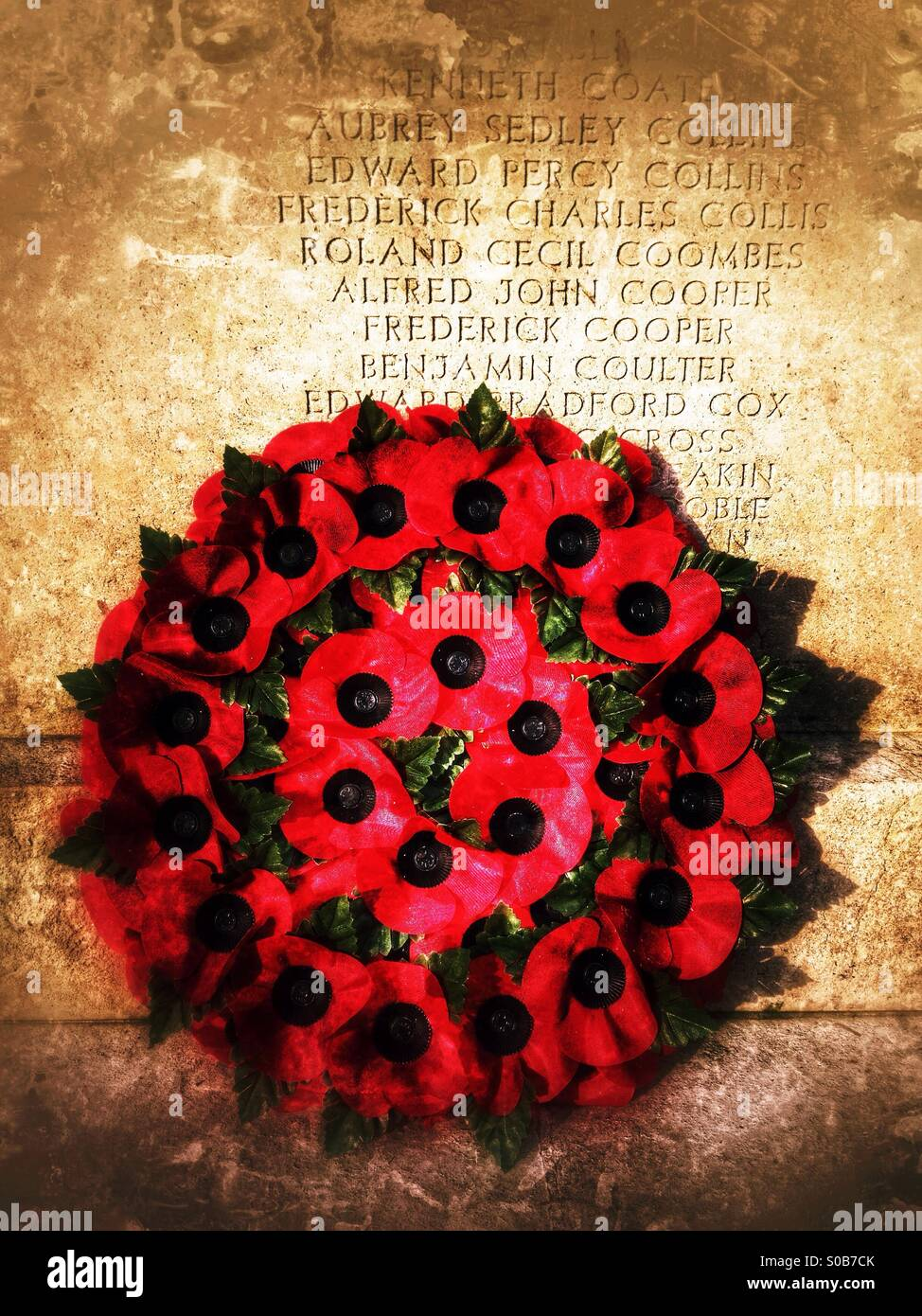 Wreath of red poppies on a war memorial. Guildford, Surrey, England. - Stock Image