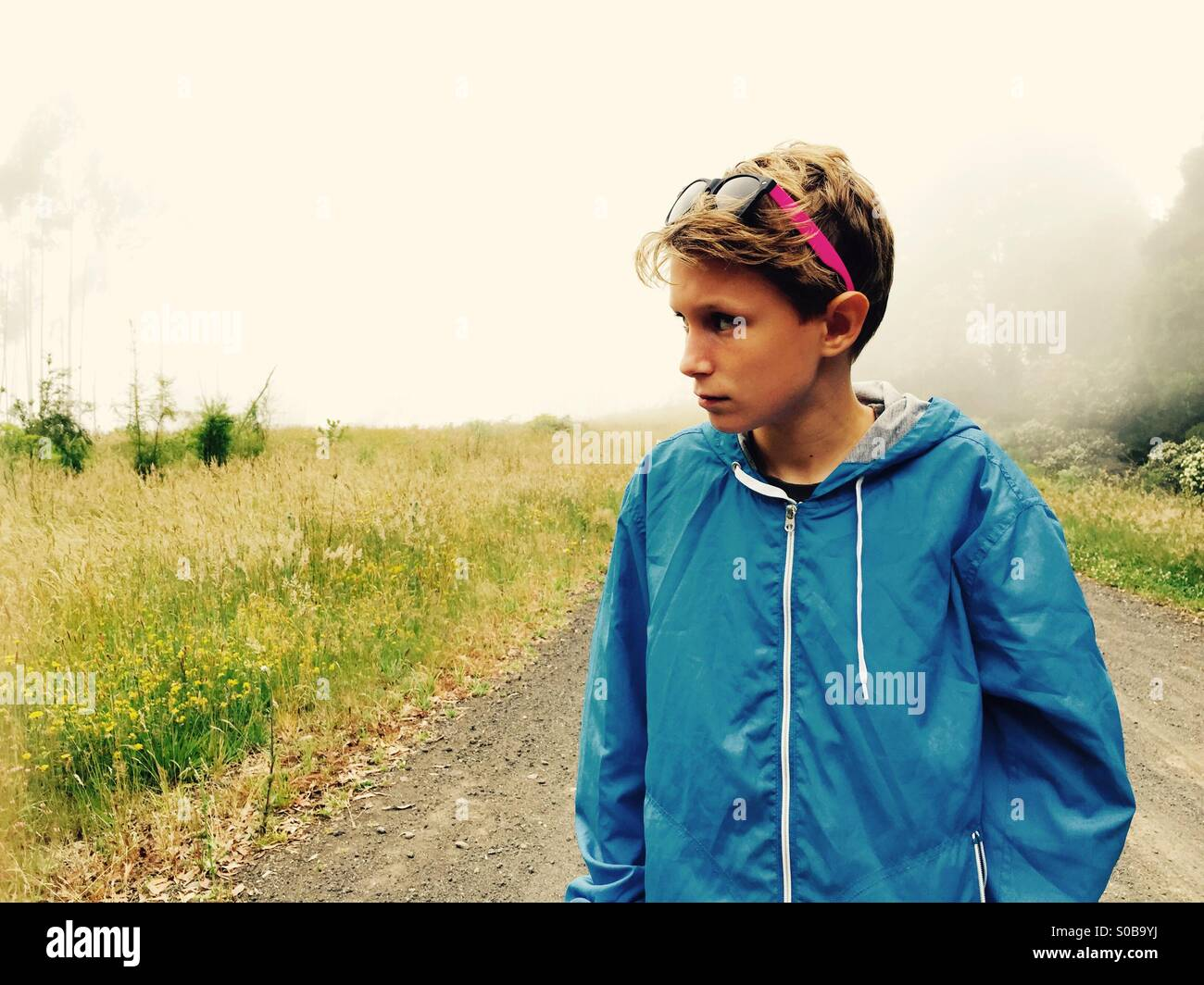 A boy walking on a country track on a foggy day - Stock Image