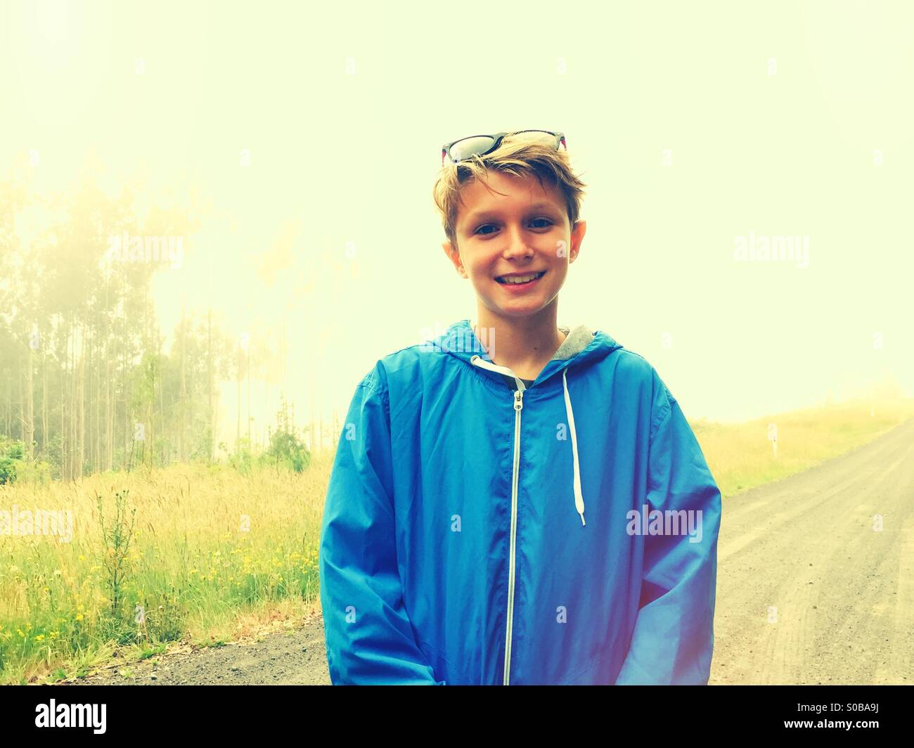 A smiling 11 year old boy photographed whilst out for a walk - Stock Image