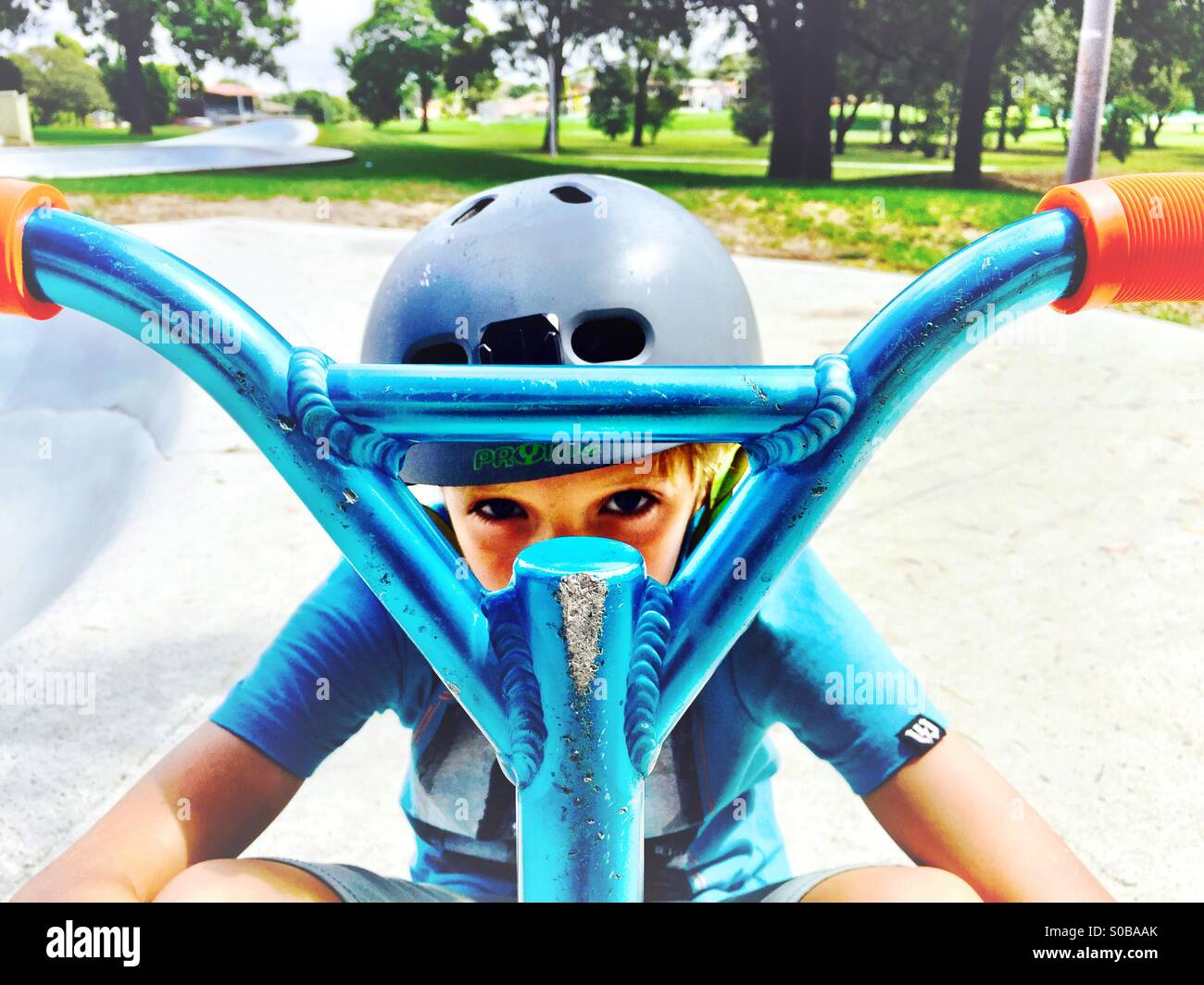A boy looking through his scooter making an 'X' shape - Stock Image