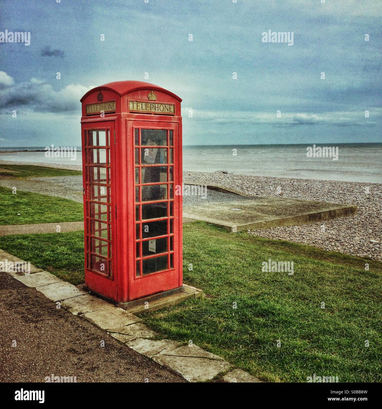 A red telephone box on the Coast - Stock Image