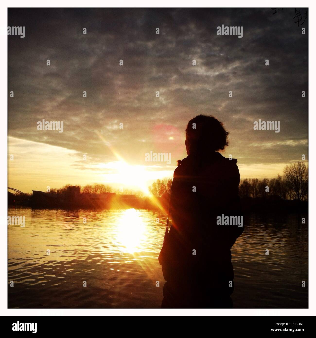 Woman standing near a lake and looking at a sunset - Stock Image