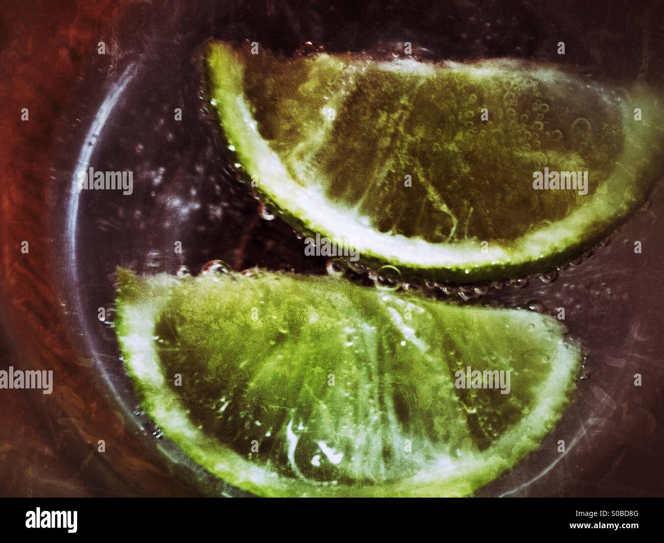 Lime slices in a glass - Stock Image