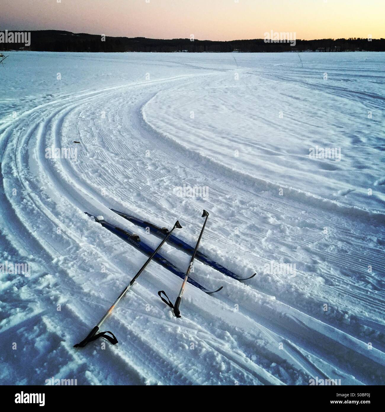 A pair of cross country skis and poles in the shape of a hashtag in some wilderness tracks on a frozen Nordic lake - Stock Image