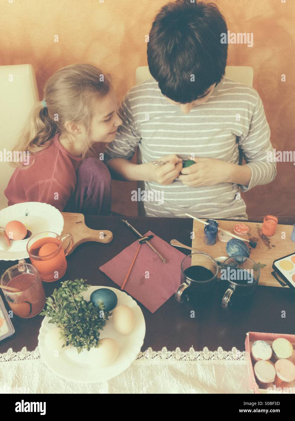Brother and sister painting Easter eggs at home - Stock Image