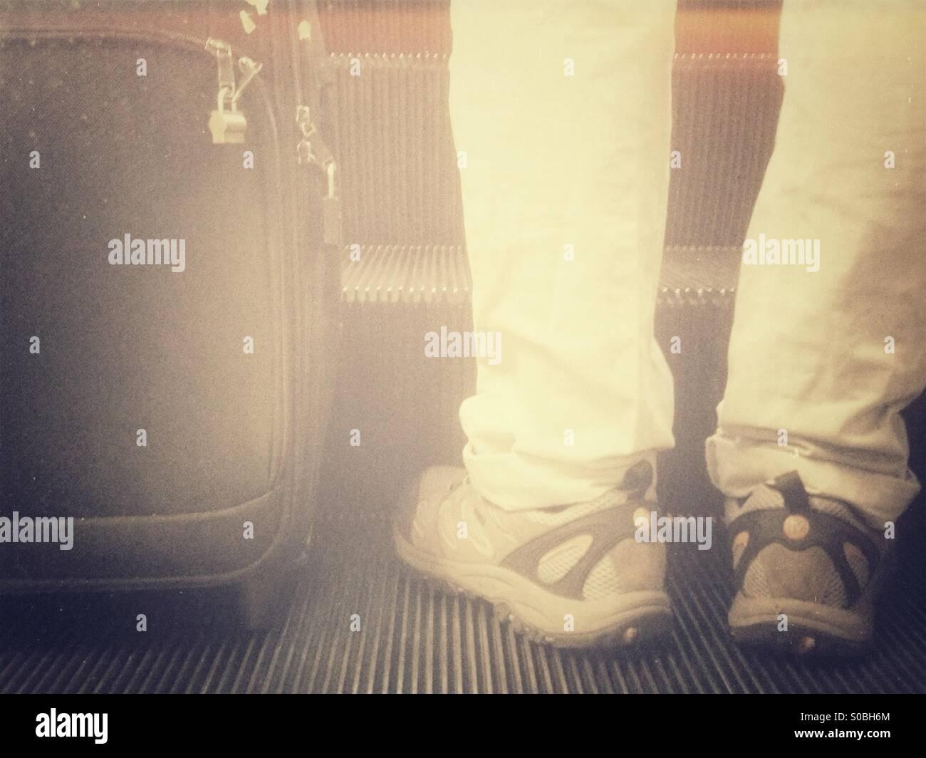 Traveler- Man with luggage on escalator - Stock Image