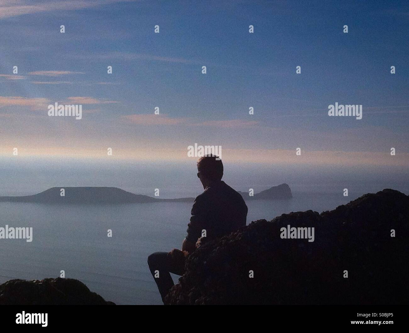 Teenager sitting on a rock overlooking  the sea near Worms head, Gower. Side view silhouette. - Stock Image