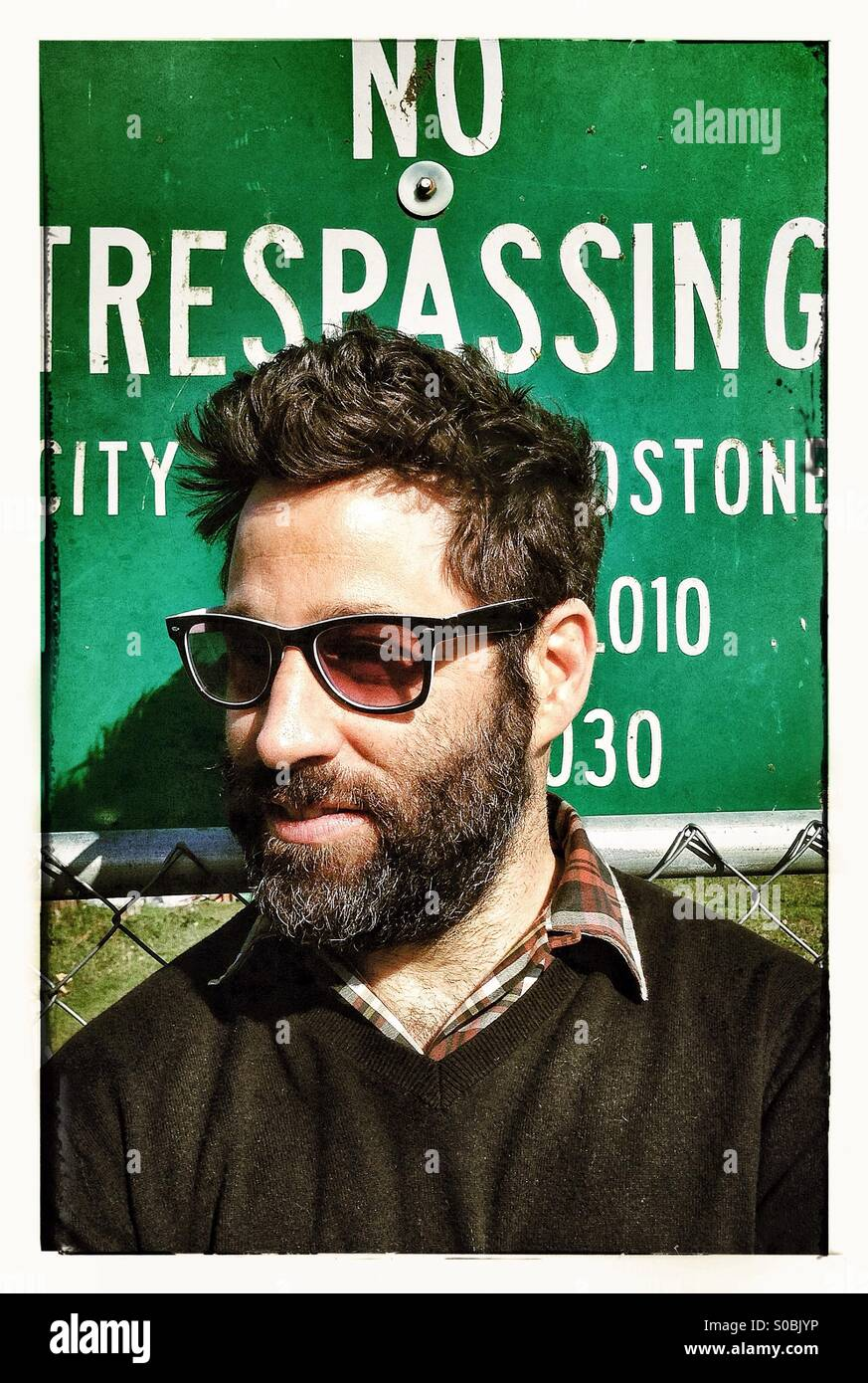 Sunglass wearing guy in front of trespassing sign - Stock Image