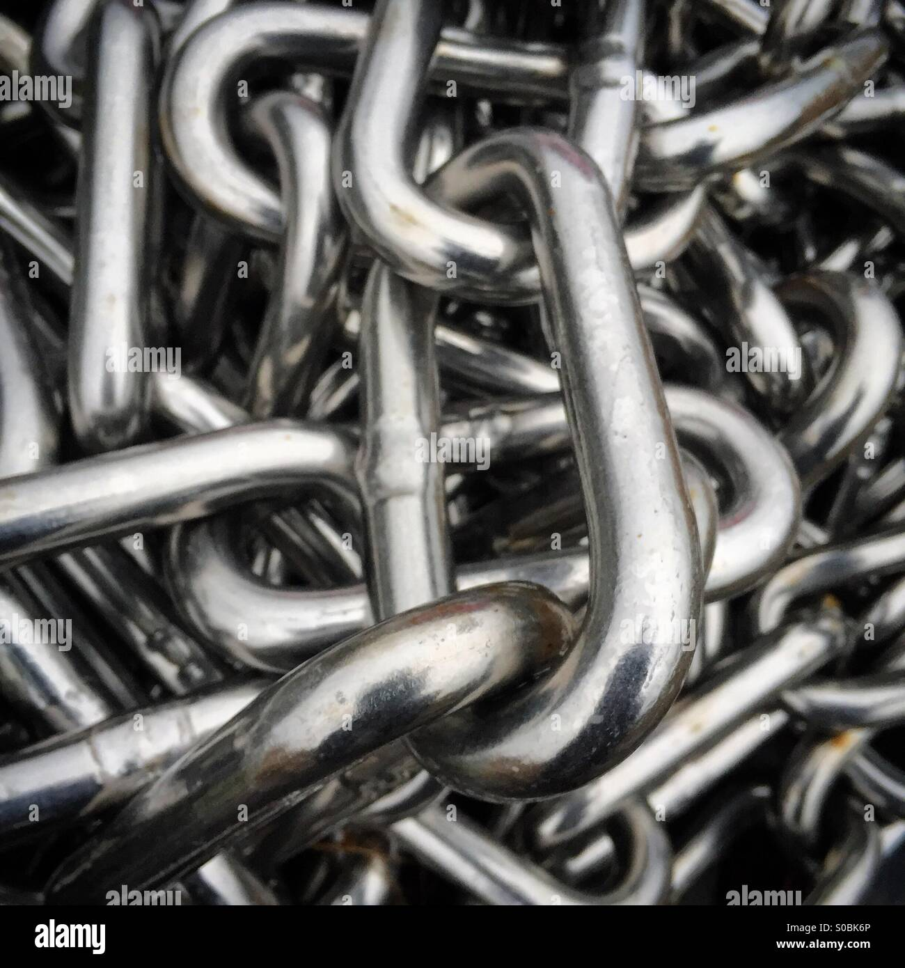 A shiny pile of metal links chain - Stock Image