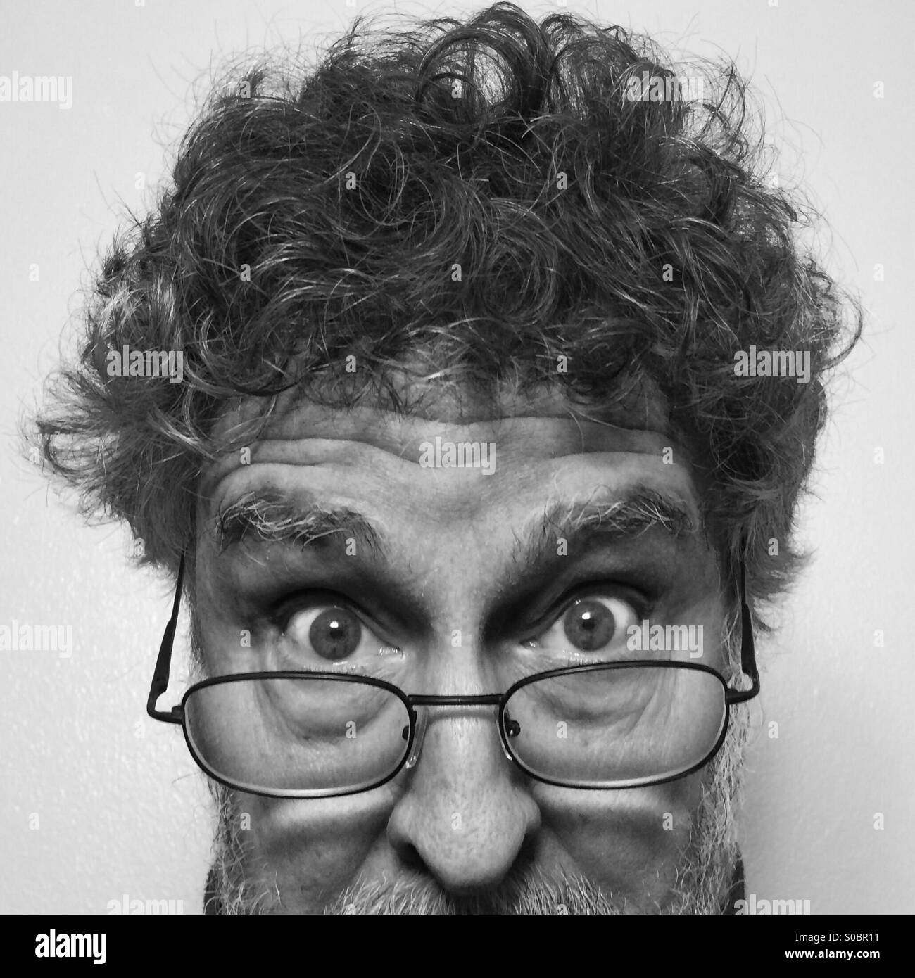 White Man, 64, bearded, wearing glasses, extreme close-up of face - Stock Image