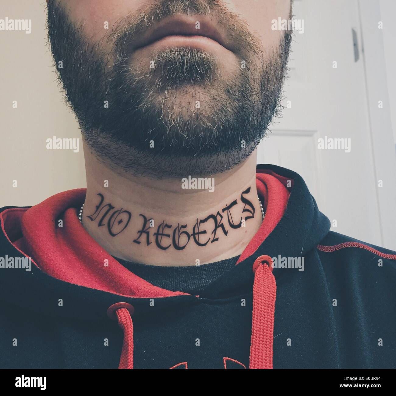 6225f1e06 White adult male with a beard and a misspelled neck tattoo wearing a red  and black