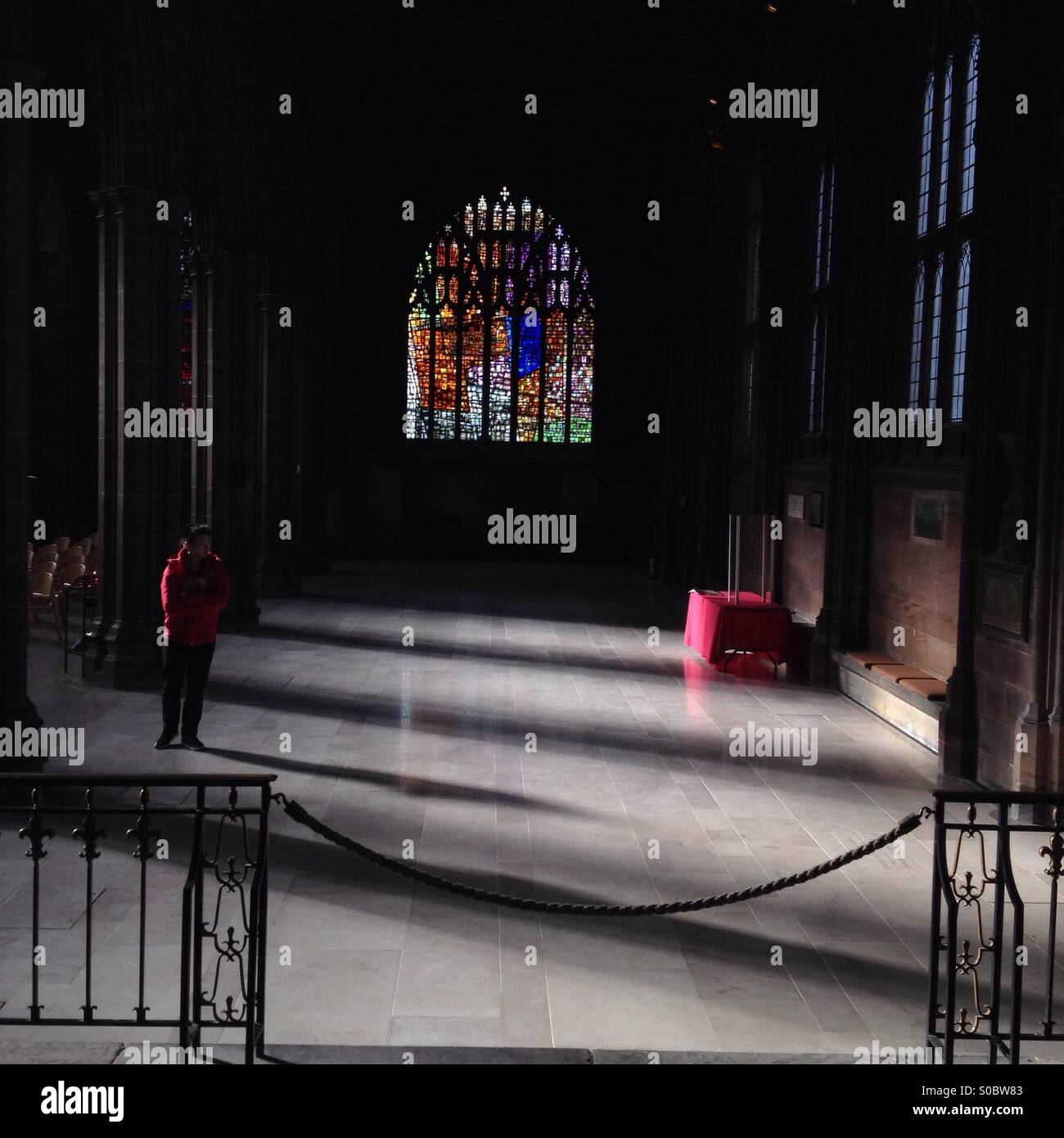 Man in front of stained glass window in Manchester Cathedral with dramatic shadows. - Stock Image