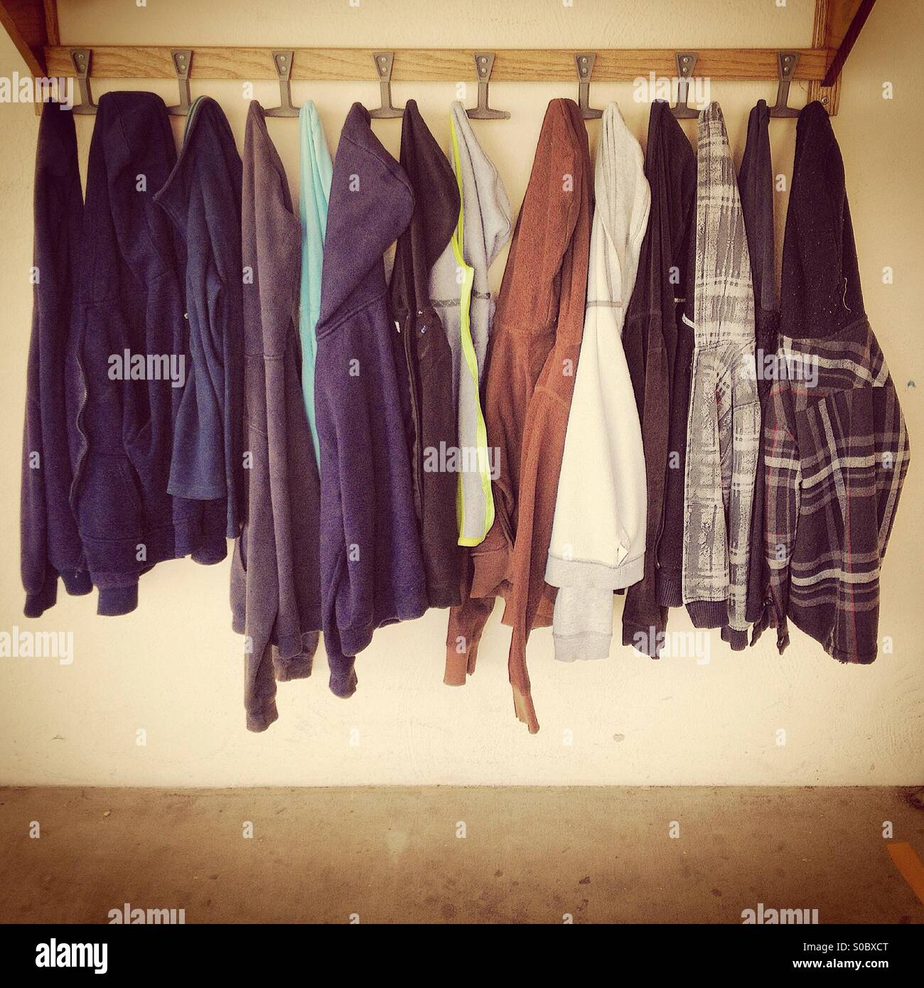 Children in junior high school jackets hanging outside classroom - Stock Image