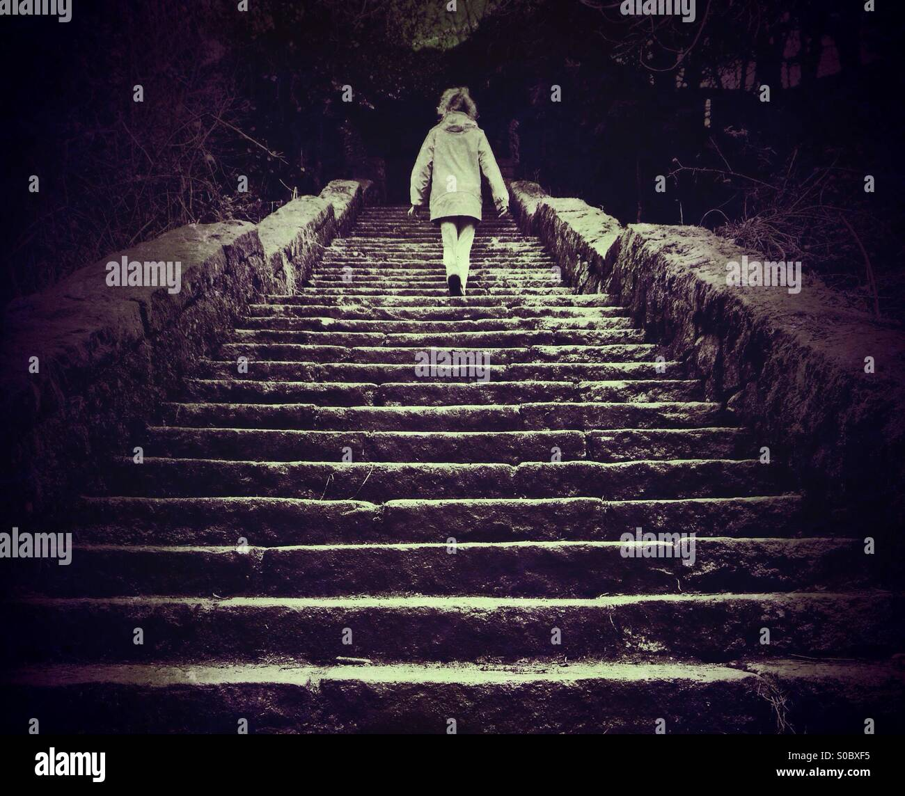 Young girl walking up old stone steps Stock Photo