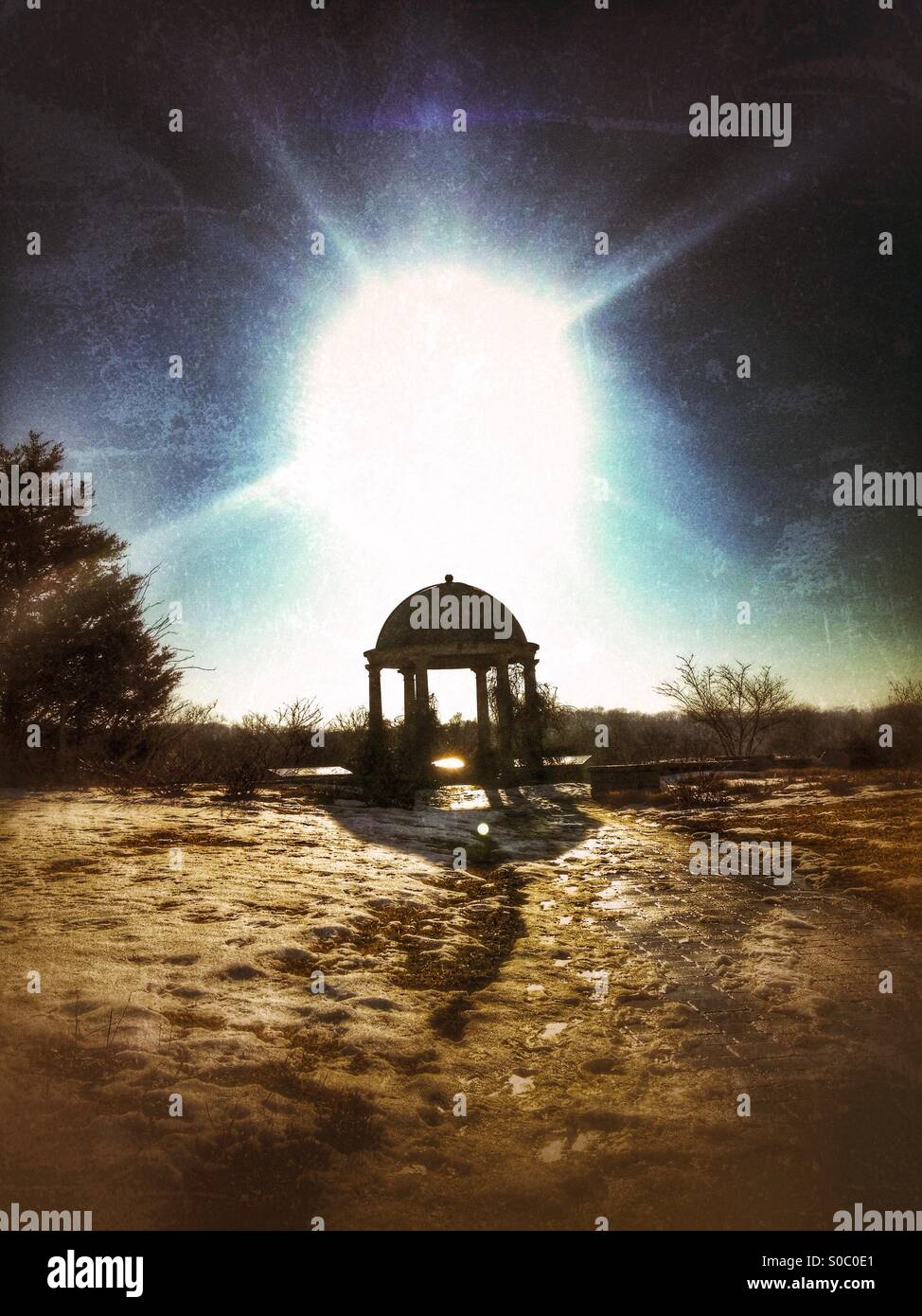 The sun beaming over a gazebo. - Stock Image