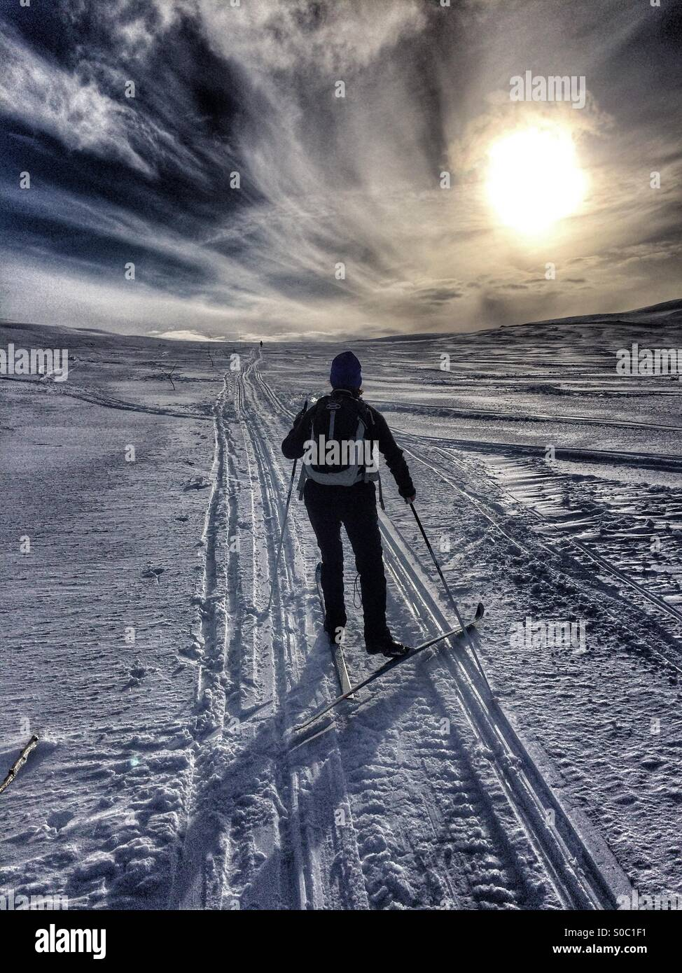 Nordic skier chasing the sun. - Stock Image