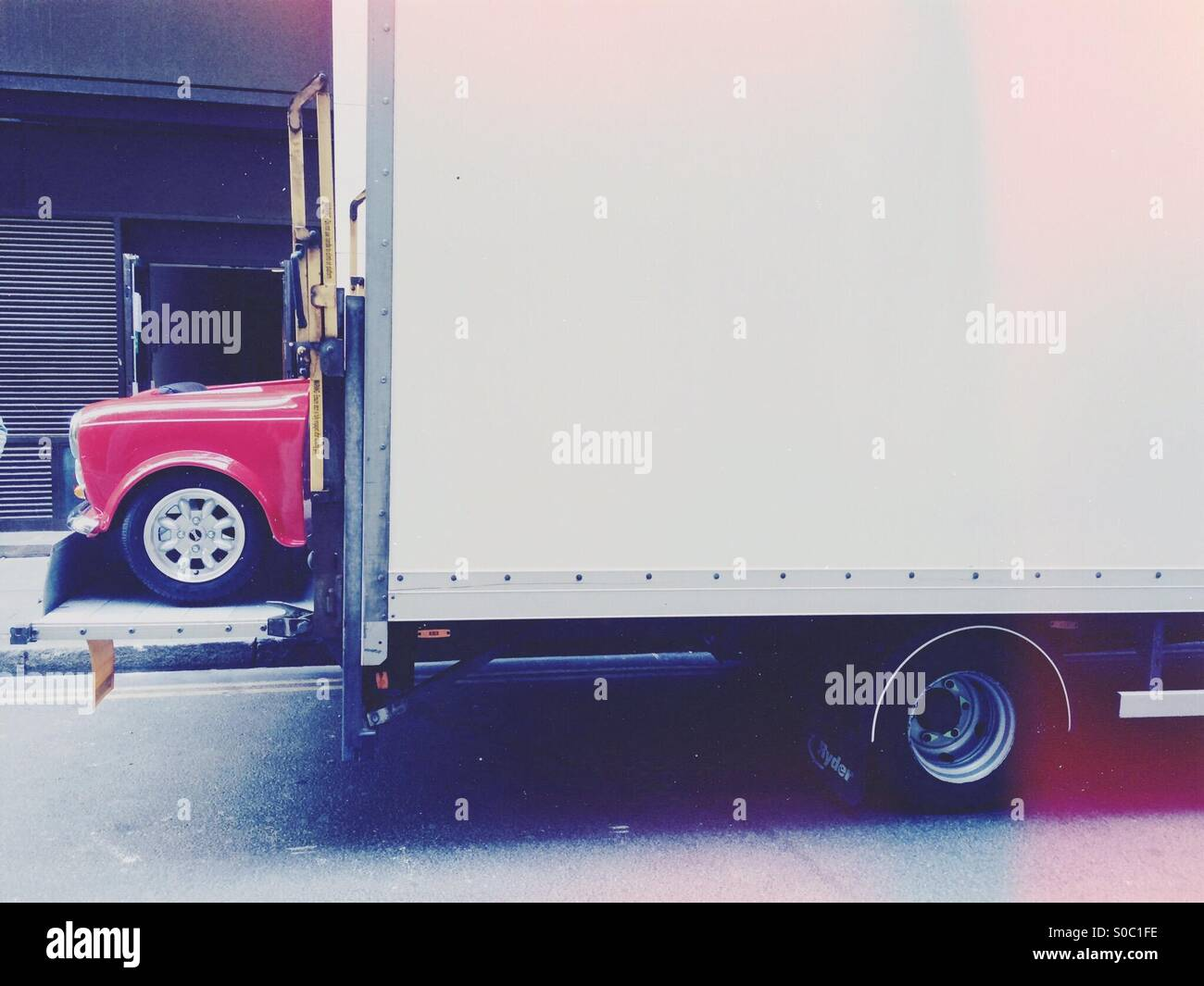Auditing Mini motor car being delivered out of the back of a lorry - Stock Image