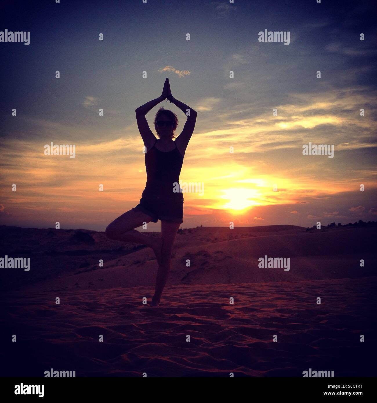 Silhouette Of Tree Yoga Pose In Front Sunset On Beach