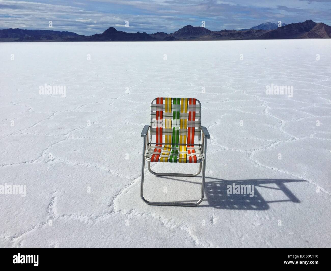 Vintage 1970s folding lawn chair sits at in the stark white Bonneville salt Flats, Utah. - Stock Image