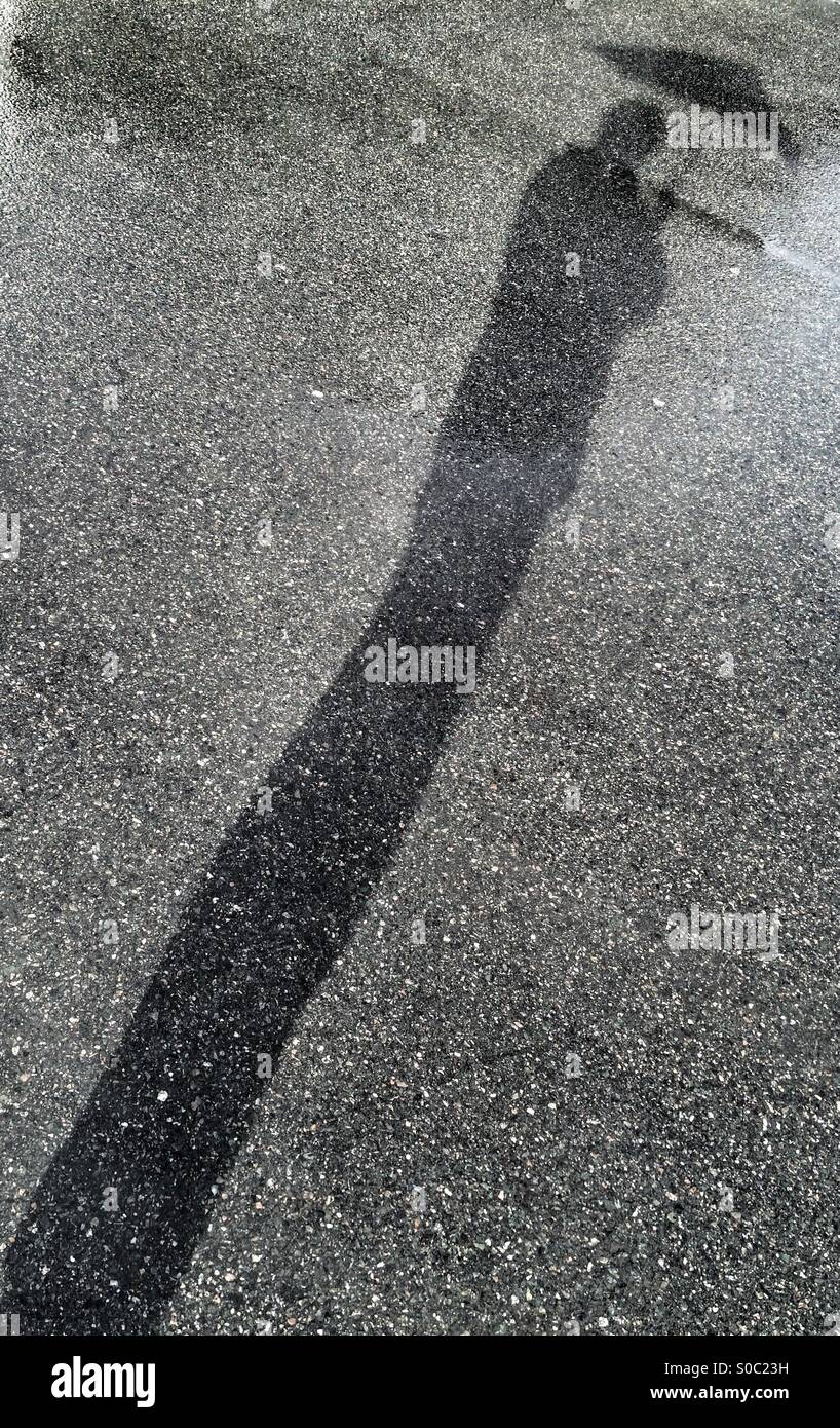 Shadow of a man with his umbrella. Stock Photo