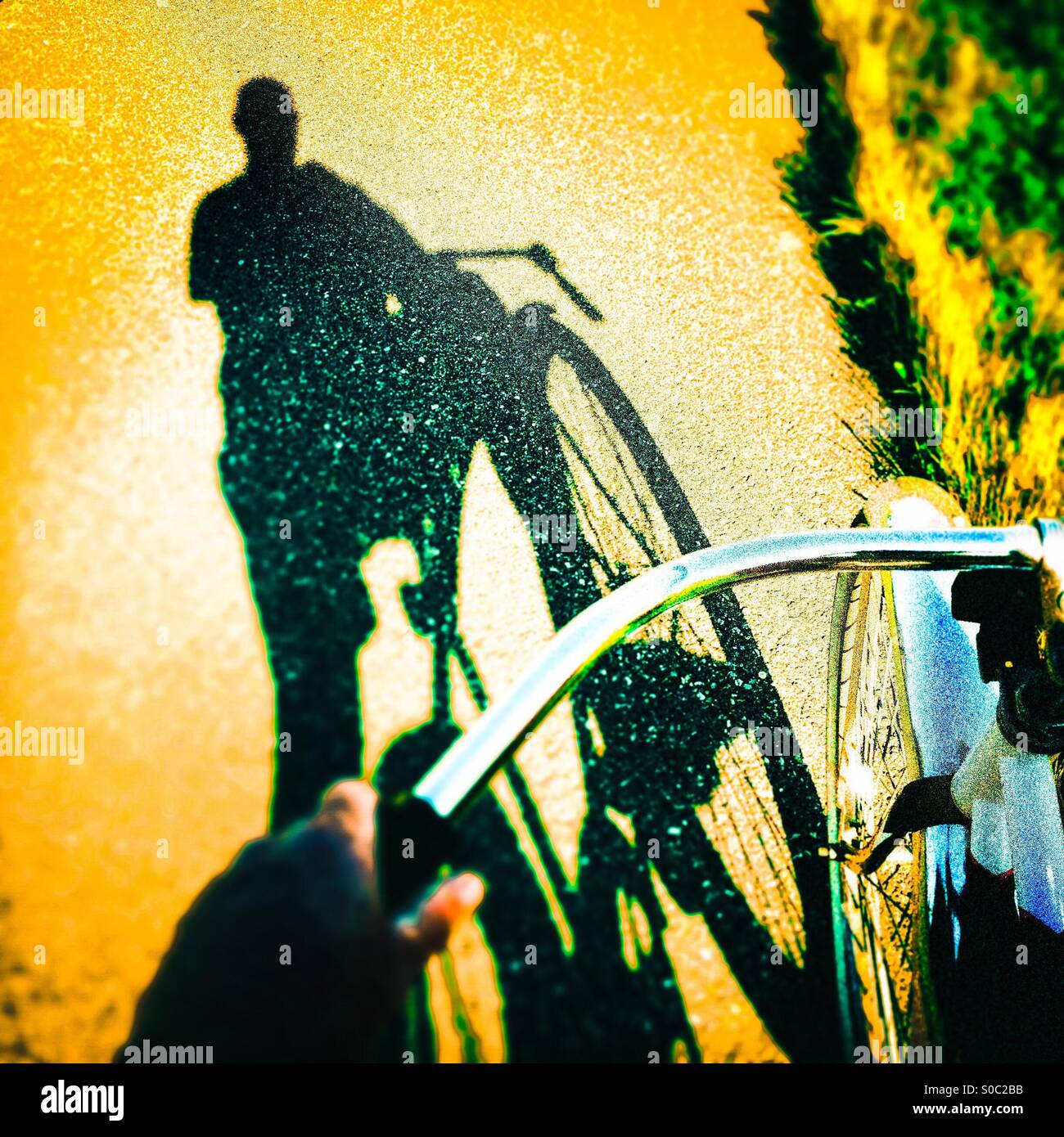 A shadow of a bike rider on a bike path. - Stock Image