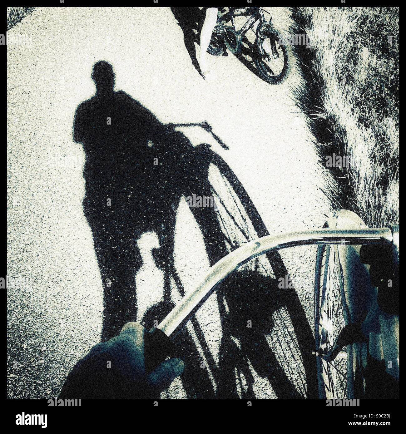 A shadow of a bike rider on a bike path talking to a child riding a bike. - Stock Image