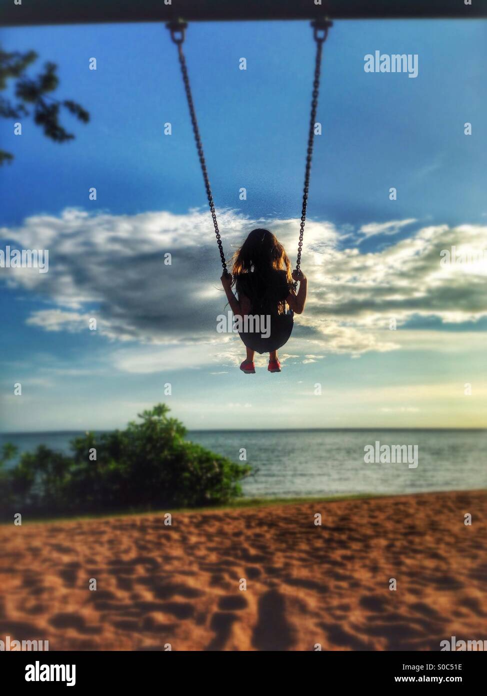 Little girl on a swing, at the beach. - Stock Image