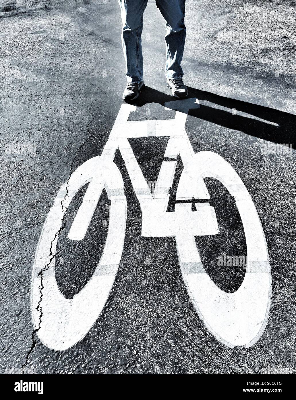 A Person Standing On Top Of A Painted Bicycle On The Ground - Stock Image