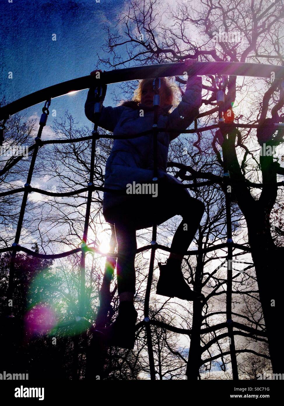 Young girl on climbing frame backlit by sun - Stock Image