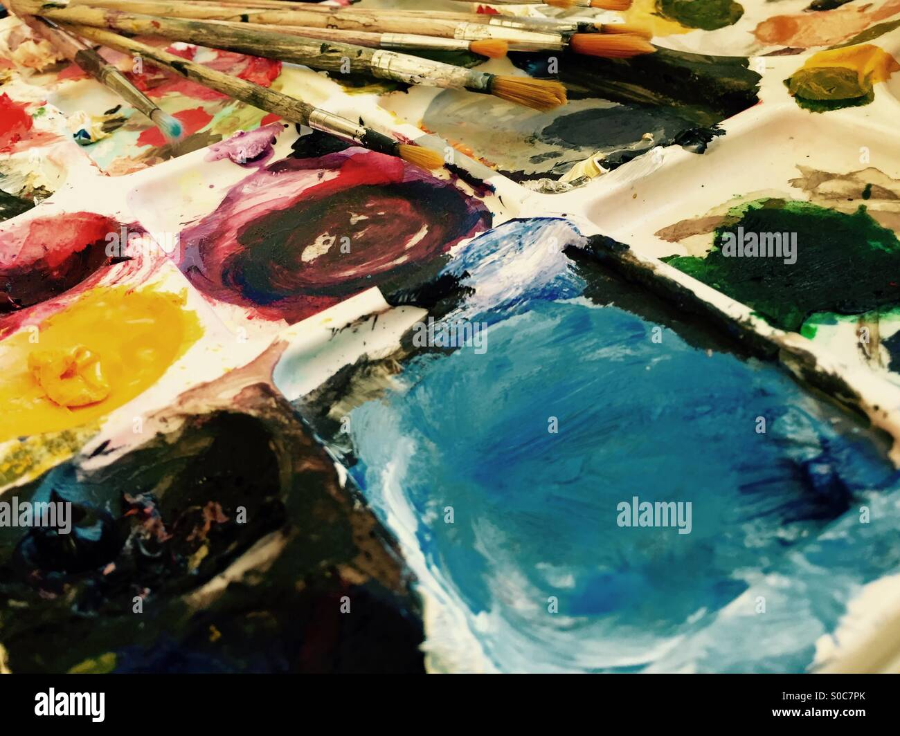 Colourful Paint pallet and brushed - Stock Image