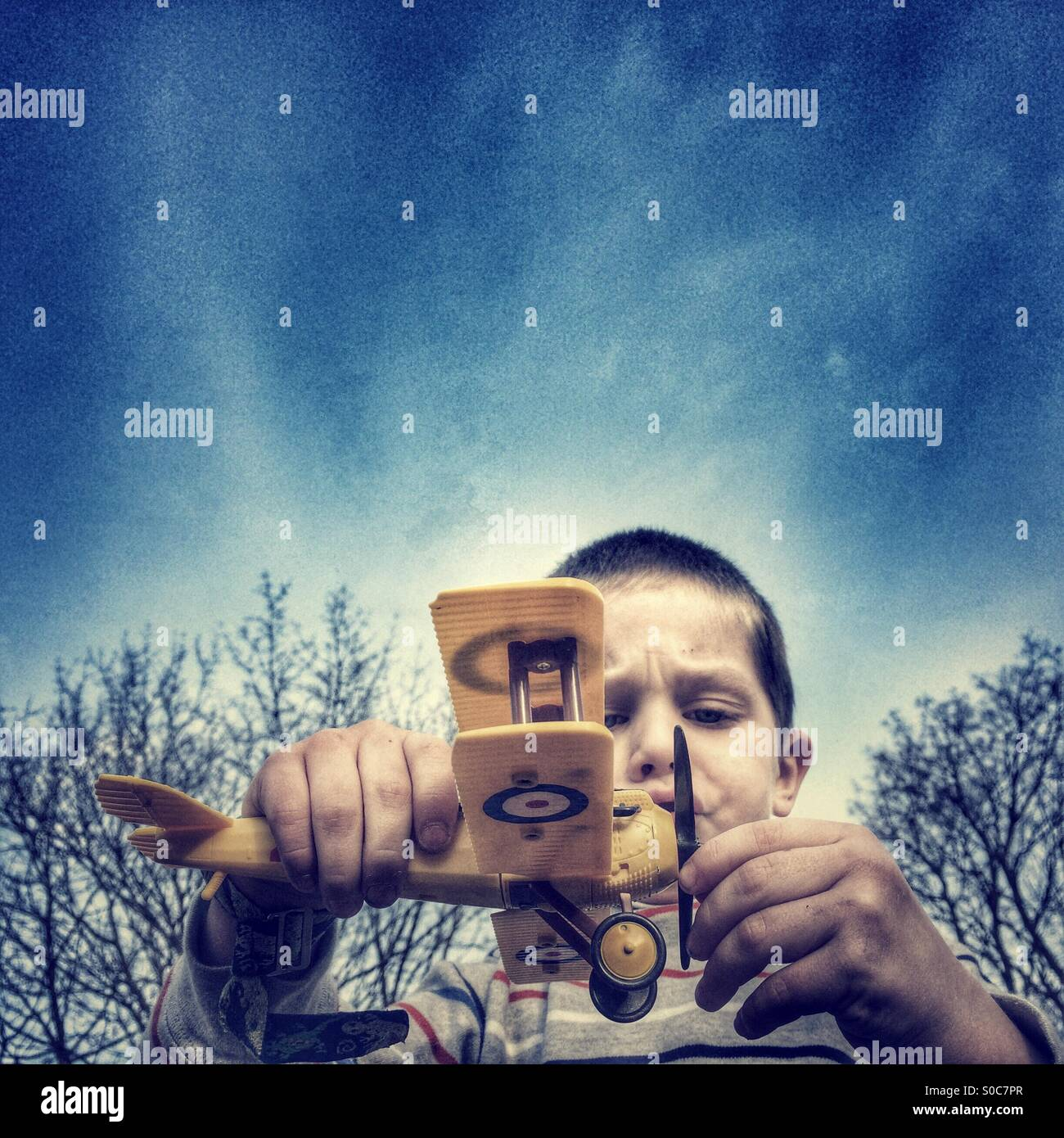 Young boy flying a model airplane - Stock Image