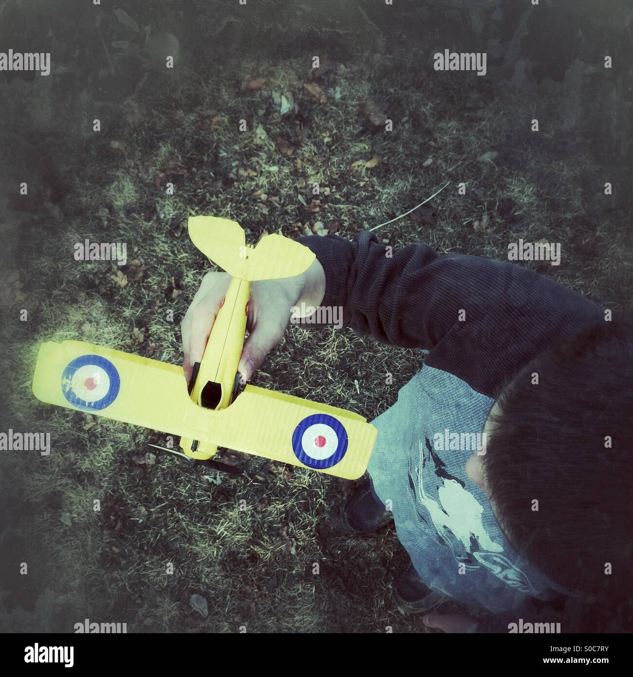 Looking down at a boy holding a model airplane - Stock Image