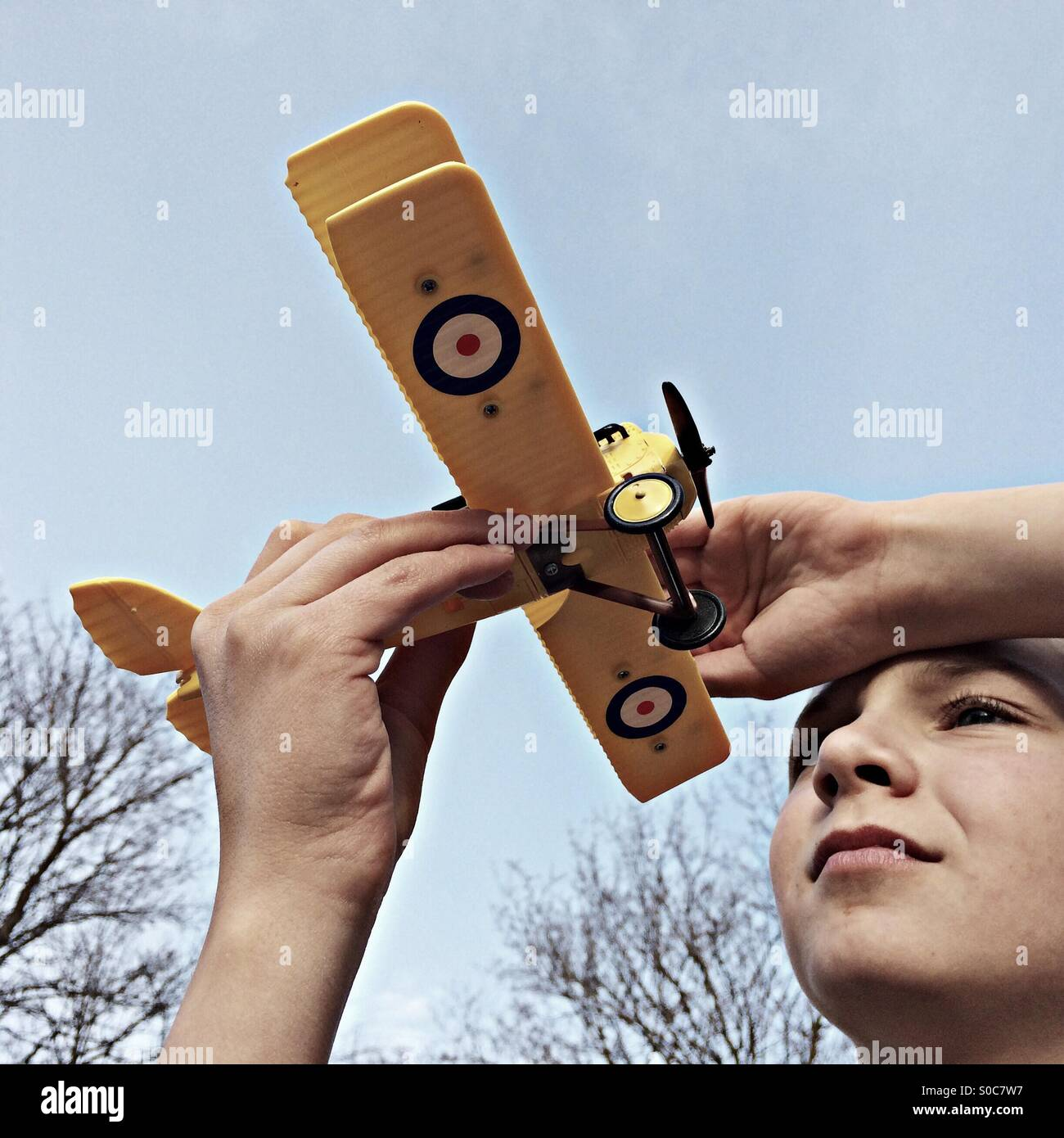 Boy holding his model biplane against the Sky - Stock Image