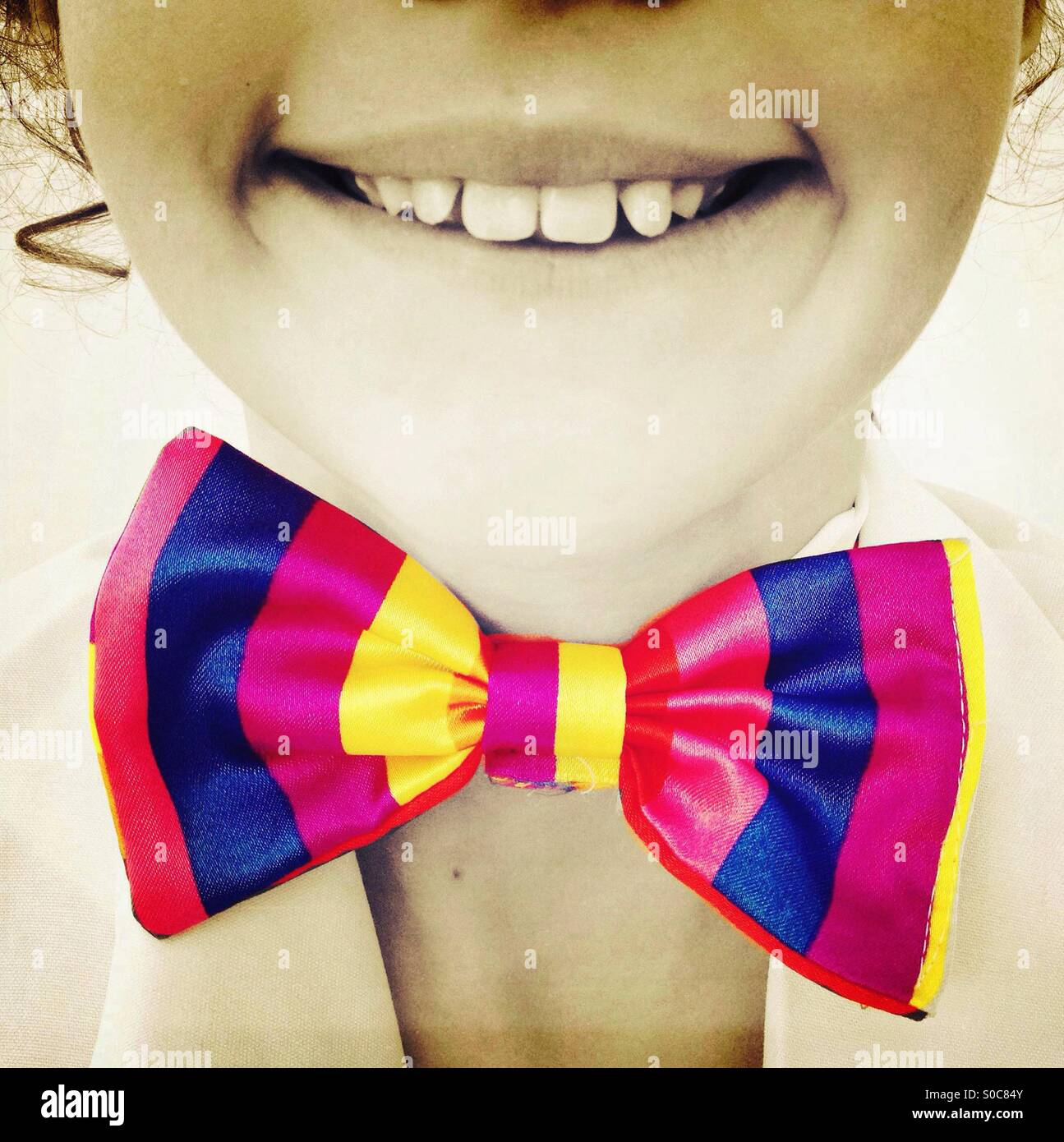 Smiling girl wearing colourful bow tie - Stock Image