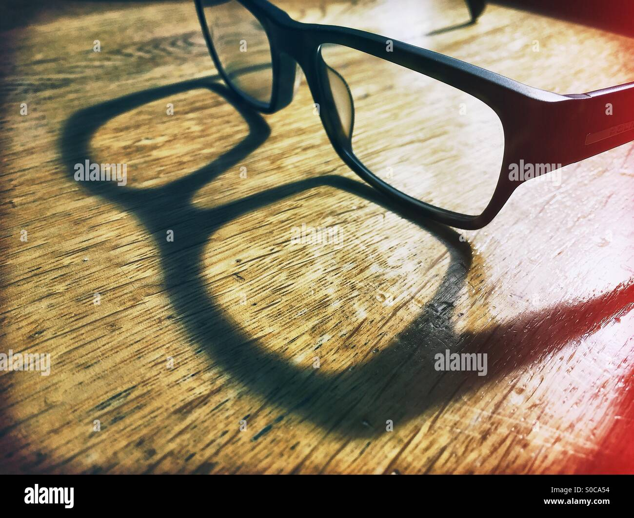 A pair of thick rimmed reading glasses sitting on a wooden desk casting a shadow in sunlight. - Stock Image