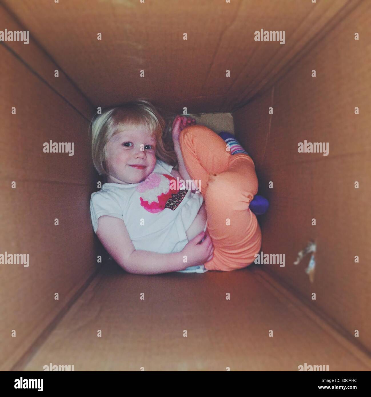 Young blond girl smiling and posing while playing in a large cardboard box. - Stock Image
