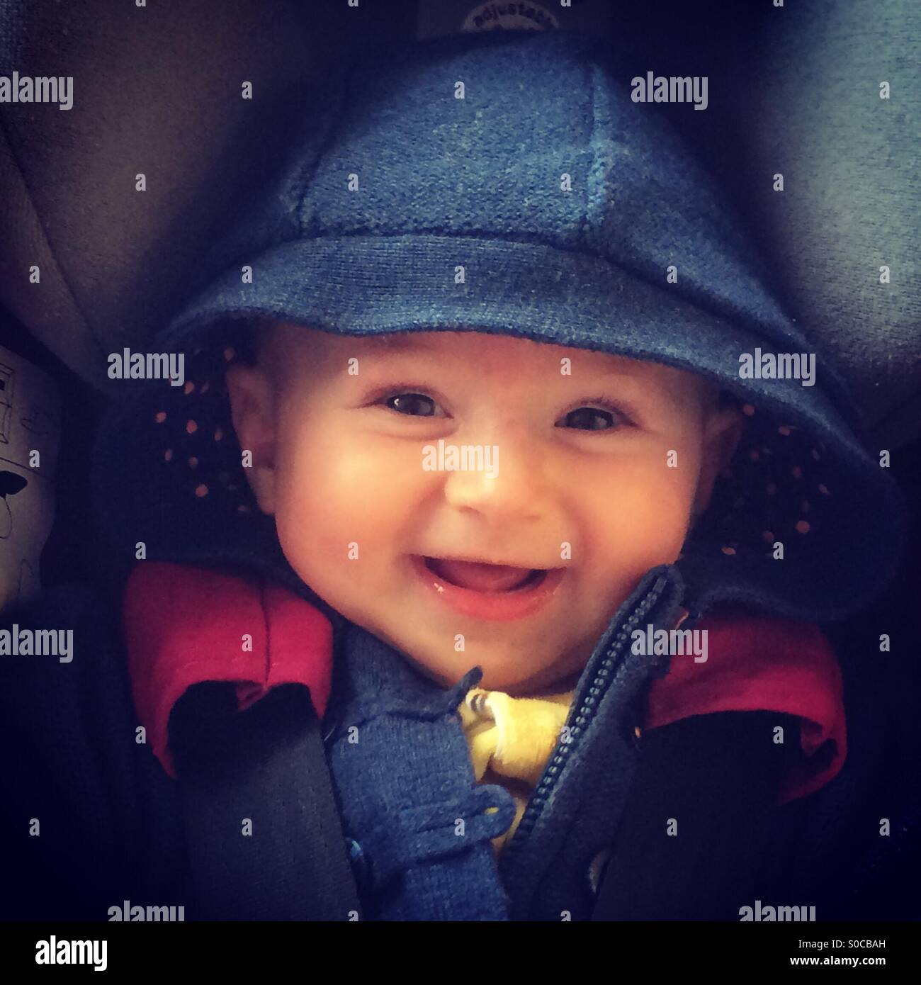 Child smiling in car seat - Stock Image