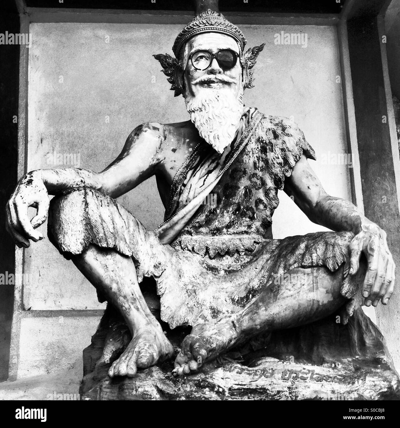 Buddhist statue wearing a sunglass. - Stock Image
