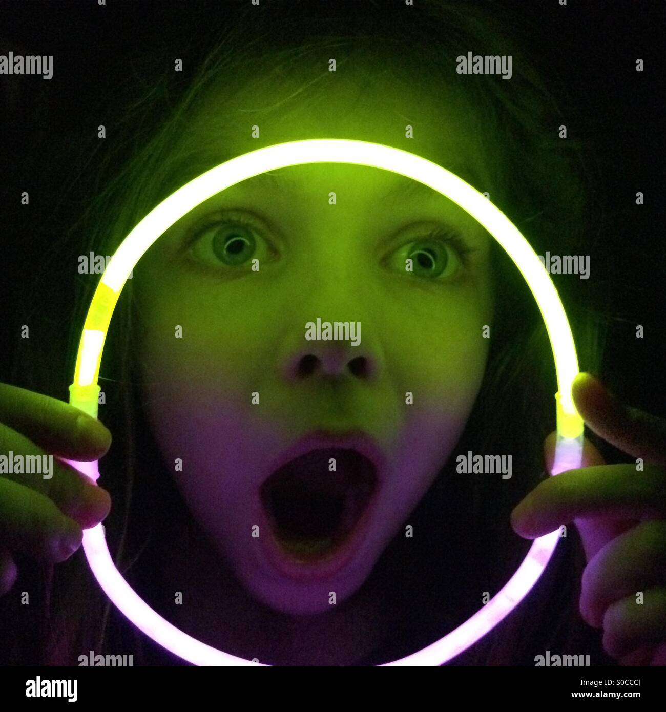 Girl making funny face looking through glow stick necklace in the dark - Stock Image