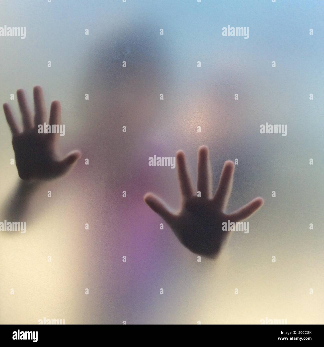 Escape - girls hand through frosted glass - Stock Image