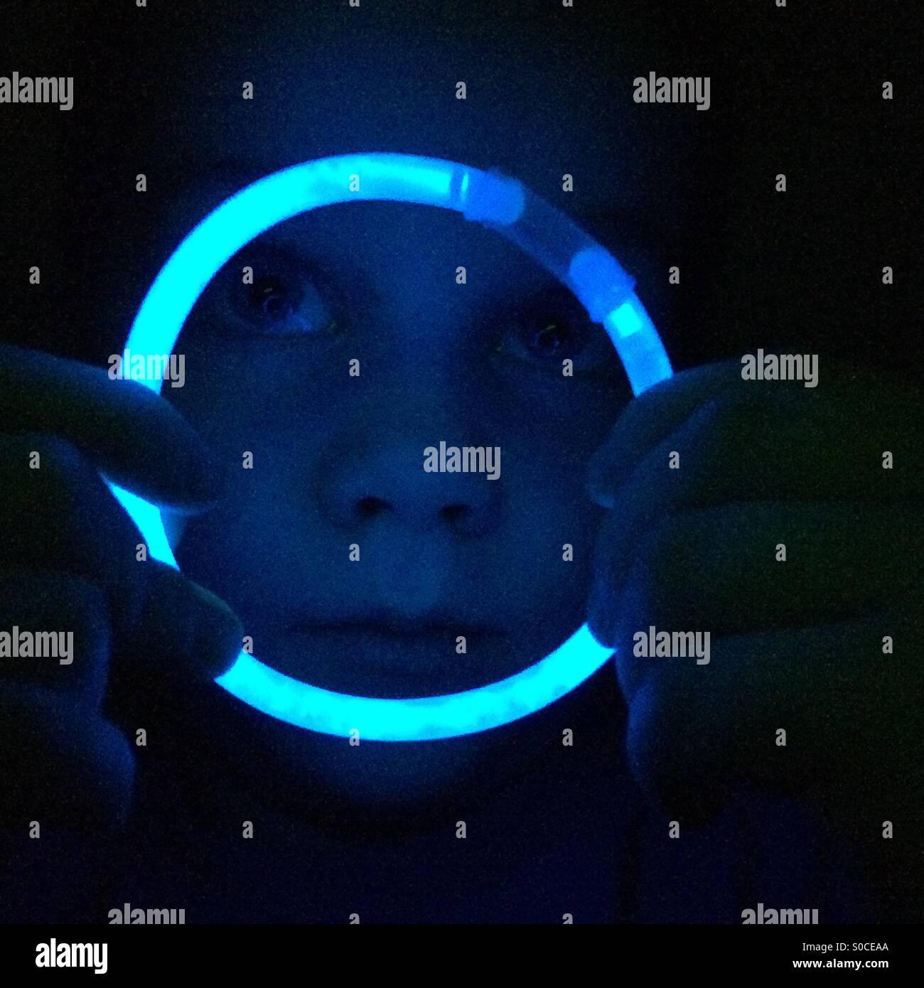 Boy looking through blue glow stick hoop - Stock Image