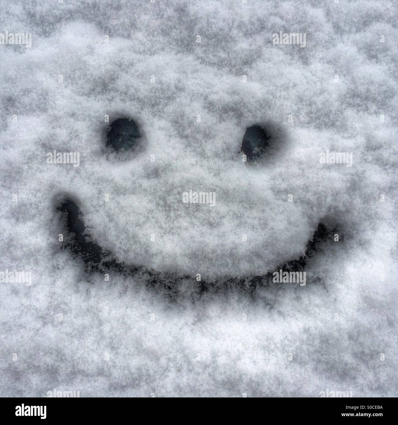 Don't worry, be happy - a smiley face drawn on a snowy car windshield - Stock Image