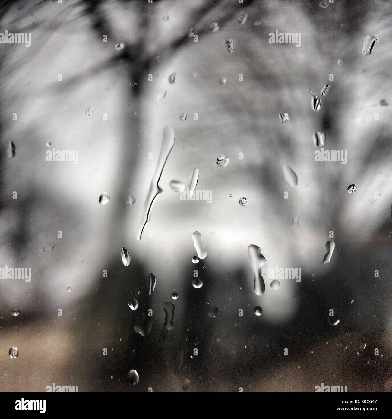 Sleet spatters on a window pane in spring - Stock Image