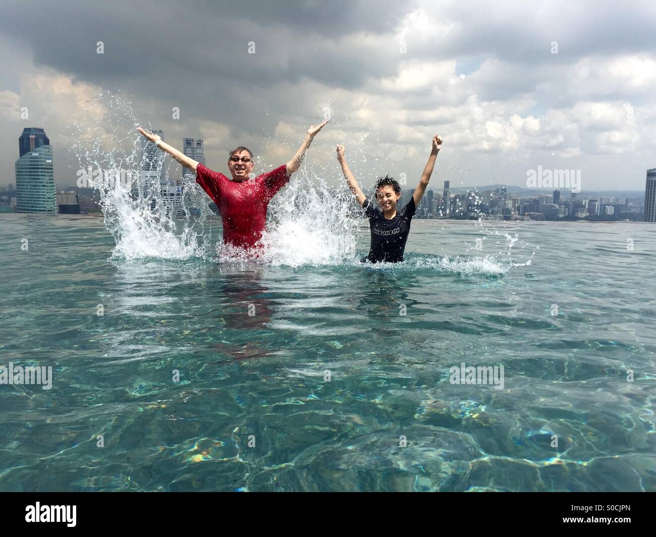 Father and son making a splash in the Infinity Pool. - Stock Image