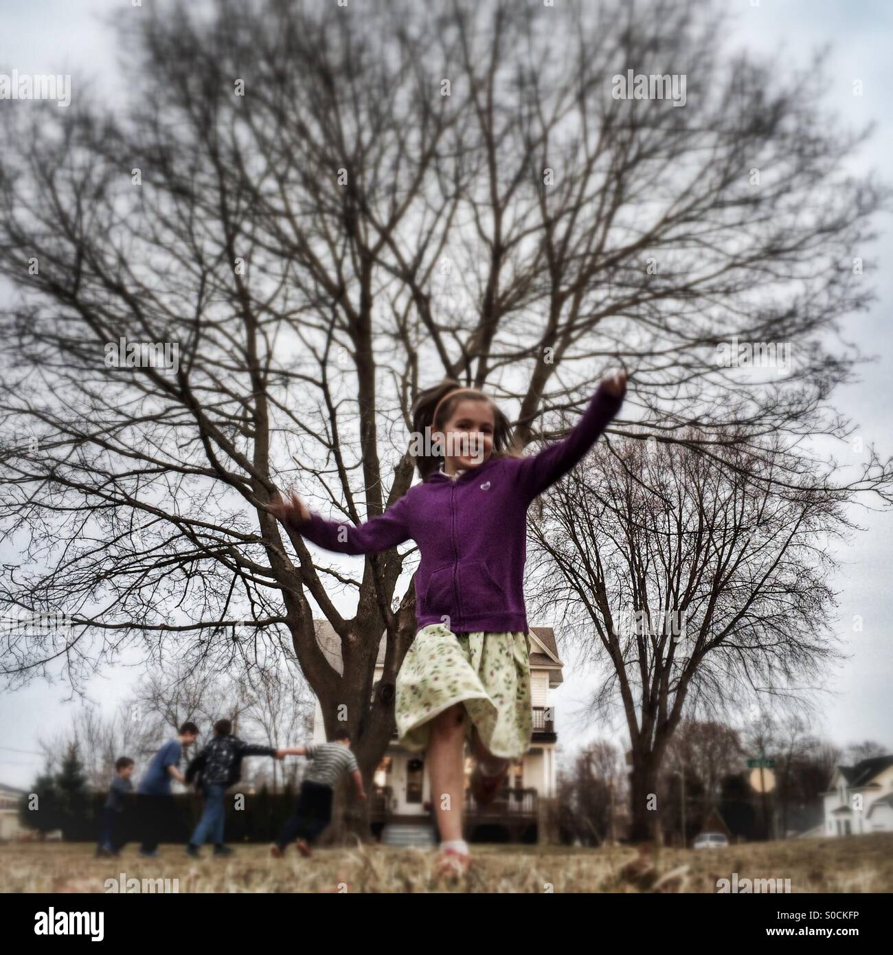 Smiling girl running through the yard, with children playing behind her; springtime fun - Stock Image