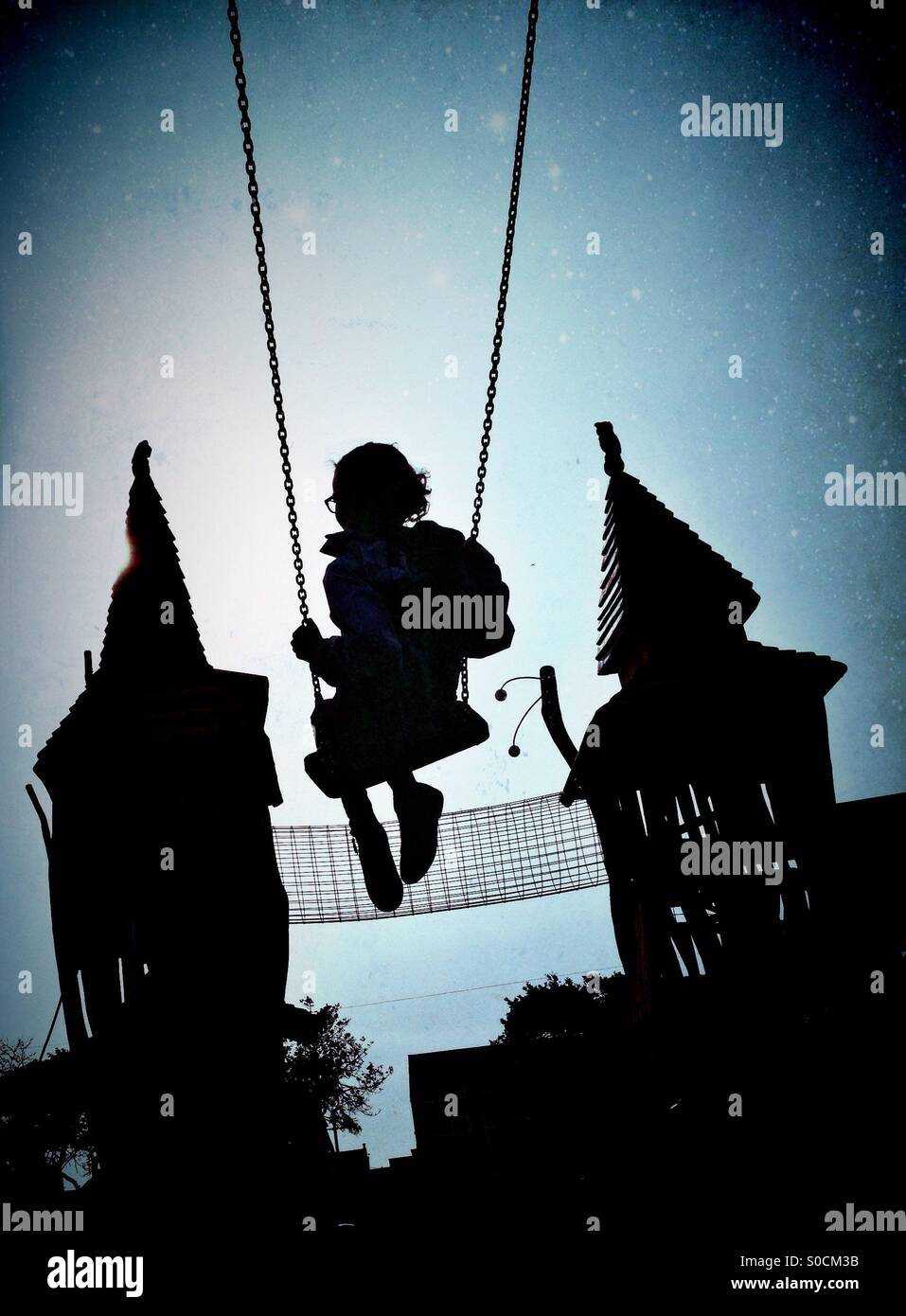 Young girl on swing in silhouette with fairytale castle in background. With dusk atmosphere and starry sky - Stock Image