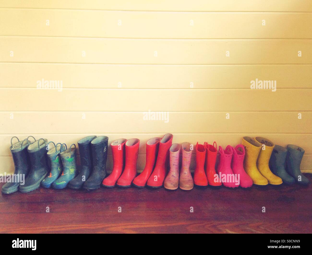 A row of children's colorful rain boots. - Stock Image