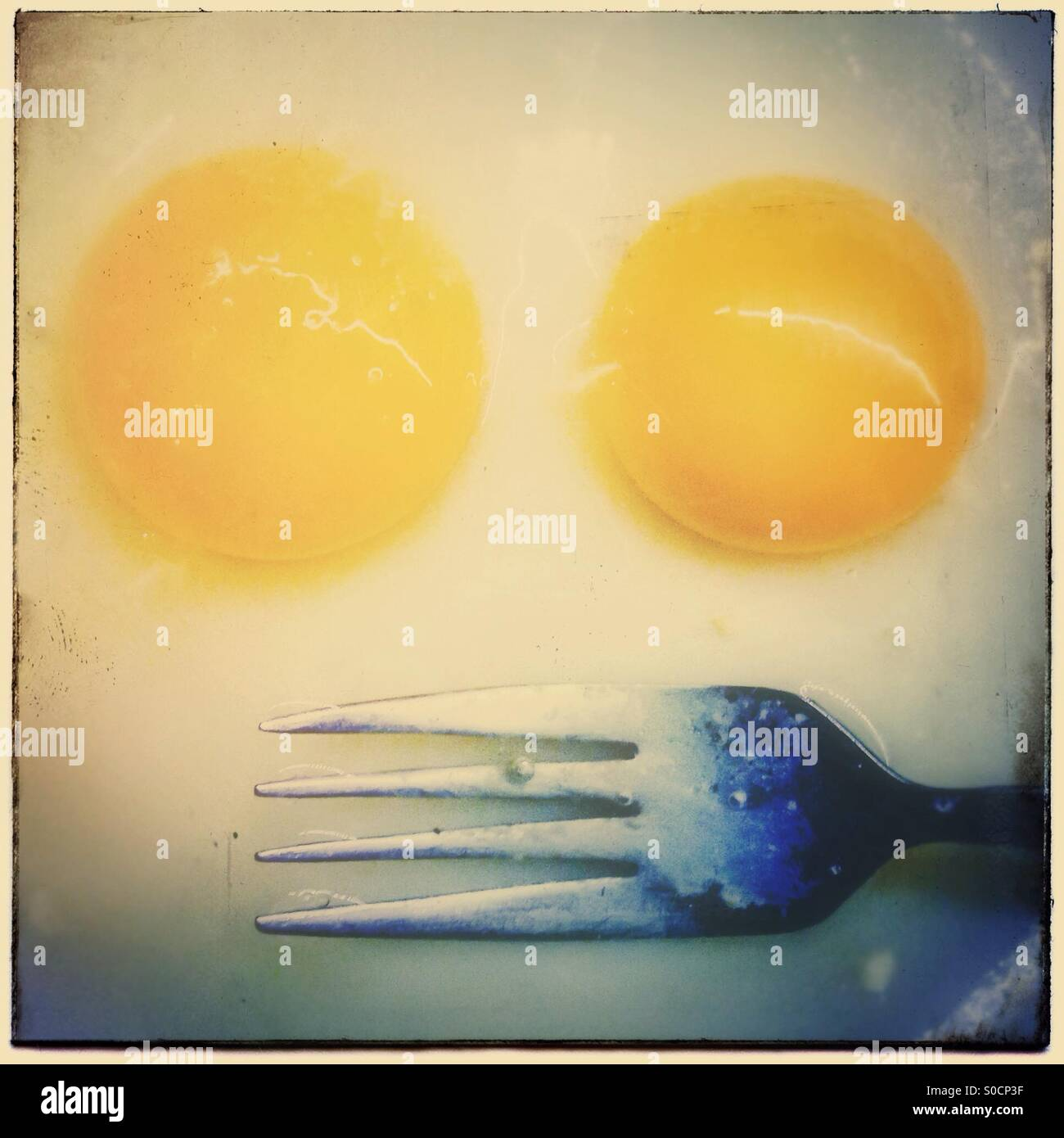 Two broken egg yolks and a fork. Faces in objects - Stock Image