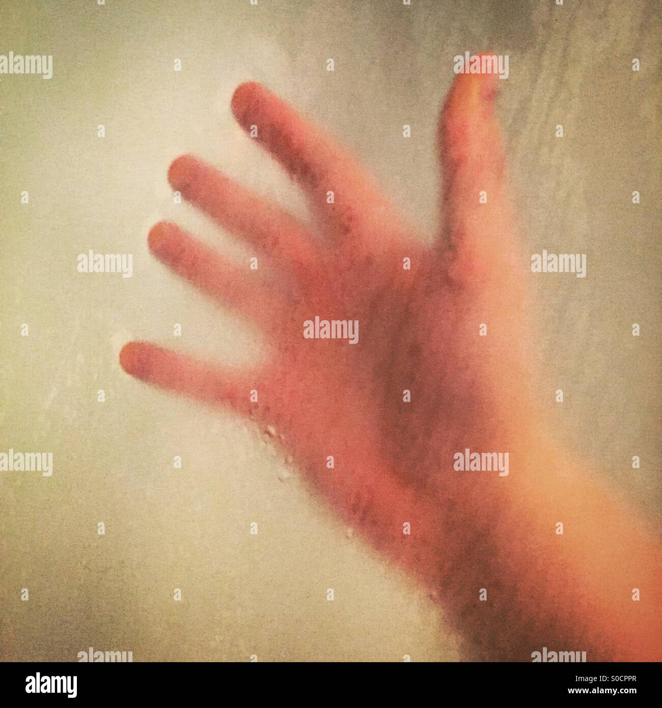 Right hand of a male resting on shower screen all condensation. - Stock Image